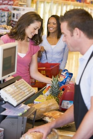 casua: Women paying for purchases at a grocery store