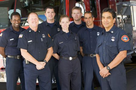 boomers: Six firefighters standing in front of fire engine with captain (depth of field)