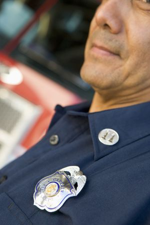 baby boomer: Fire captain with badge standing near fire engine (selective focus)