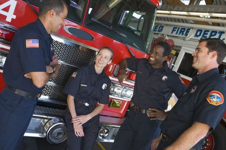 colo: Four firefighters talking by fire engine