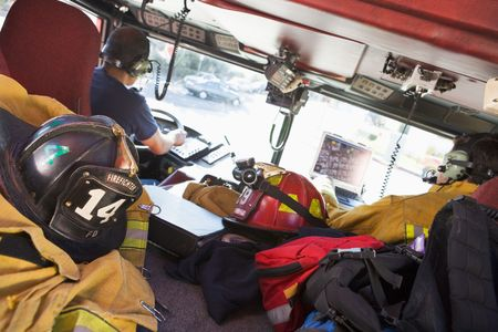 colour images: Two firefighters driving a fire engine with gear in the back (selective focus) Stock Photo