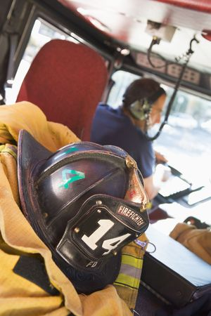 Firefighting gear in the back of a fire engine with fireman in background (selective focus)