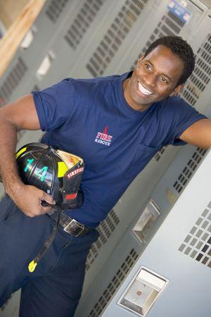 colour images: Fireman holding helmet standing by locker in fire station locker room (depth of field) Stock Photo