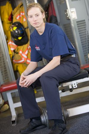 colour images: Firewoman sitting on bench in fire station locker room Stock Photo