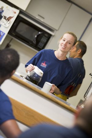 boomers: Four firefighters in break room with one getting coffee (selective focus)