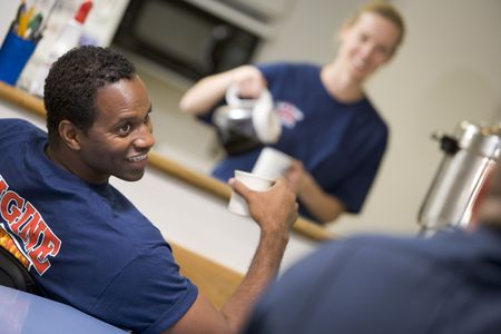 baby boomer: Three firefighters in break room with one getting coffee in background (selective focus)