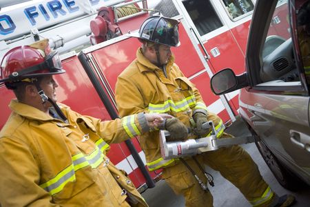 Two firemen using the jaws of life on a car door Stock Photo