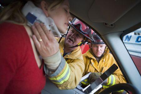 personas ayudando: Ayudar a los bomberos mujer con cuello ortopédico, mientras que otro bombero utiliza las fauces de la vida en la puerta de un automóvil (atención selectiva)