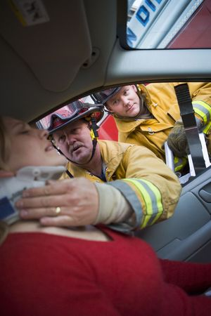 boomers: Fireman helping woman with neck brace while another fireman uses the jaws of life on a car door (selective focus) Stock Photo