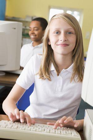 Student na terminál počítače psaní s studentů v pozadí (selektivní focus)