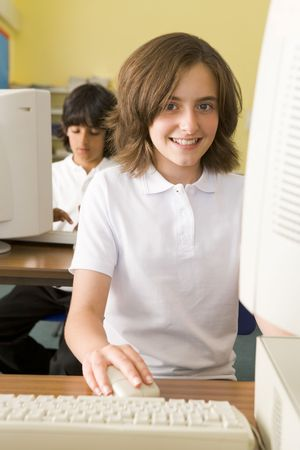 schoolmate: Student at computer terminal with student in background (selective focus)