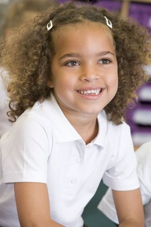 caucasian appearance: Student in class sitting on floor smiling (selective focus)