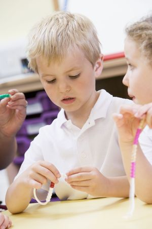 schoolmate: Students in math class using counting beads (selective focus)