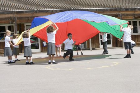 recess: Students outdoors during recess playing with a parachute