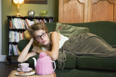 tea breaks: Young woman lying on sofa at home