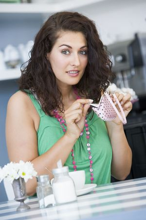 change purse: Young woman sitting at a table checking change purse