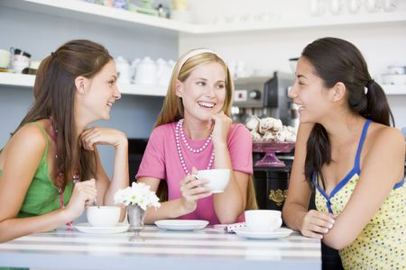 young woman sitting: Three young woman sitting at a table and drinking tea
