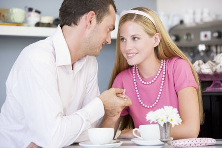 affectionate actions: Young couple sitting at a table and having tea together