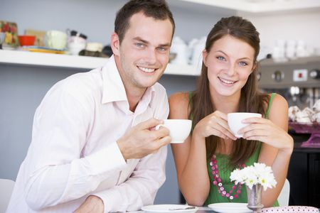 casua: Young couple sitting at a table and having tea together