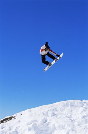sporting activity: Snowboarder doing jump on hill Stock Photo