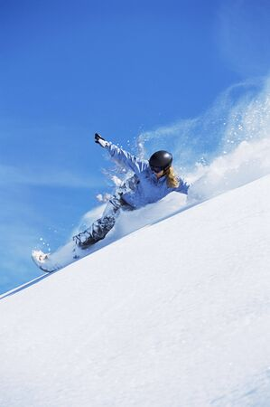 Snowboarder coming down hill photo
