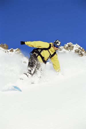 sporting activity: Snowboarder coming down hill smiling