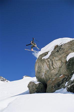 salto largo: Esquiador saltando fuera acantilado (lejos)