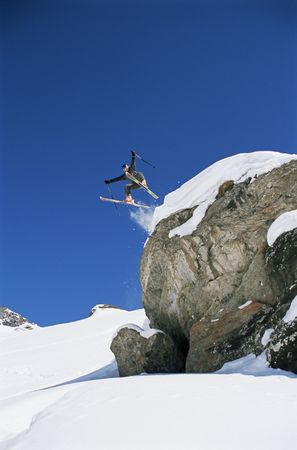 Skier jumping off cliff (far away) photo