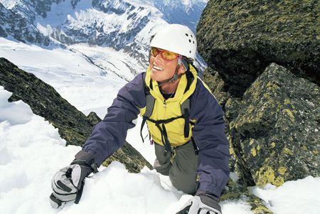 Mountain climber coming up snowy mountain smiling (selective focus) photo