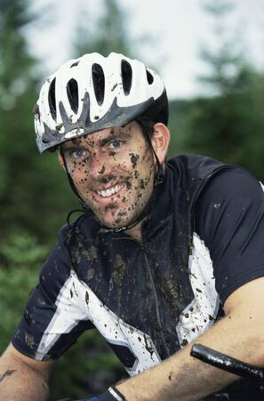 moto da cross: L'uomo seduto all'aperto in bicicletta sporco e sorridente (messa a fuoco selettiva)