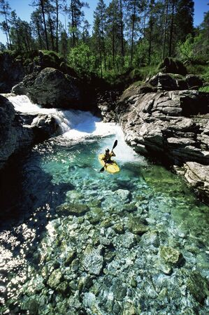 messze: Kayaker in calm water near waterfall (far away)