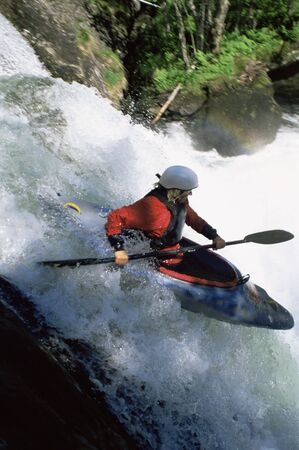 canoeist: Kayaker in rapids going over waterfall (blur)