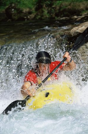 caucasoid race: Kayaker coming down small waterfall (selective focus)