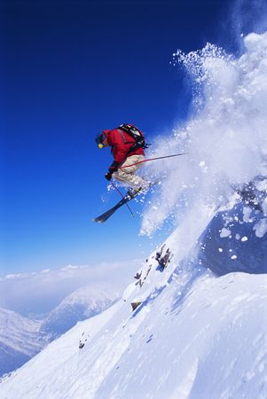 skieer: Skiër springen over besneeuwde heuvel Stockfoto