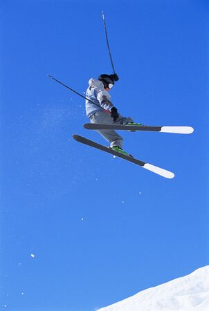 Skier doing jump on snowy hill photo