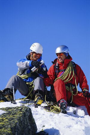 Two mountain climbers sitting on snowy mountain drinking from thermos and smiling (selective focus)