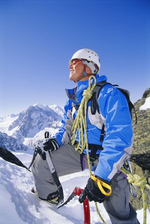 Mountain climber coming up snowy mountain smiling photo