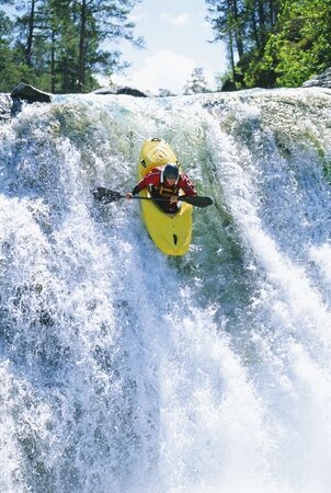 Kayaker in rapids coming over waterfall (selective focus) photo