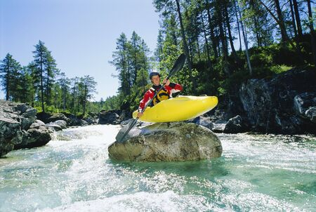 the rapids: Kayaker on top of rock in rapids smiling