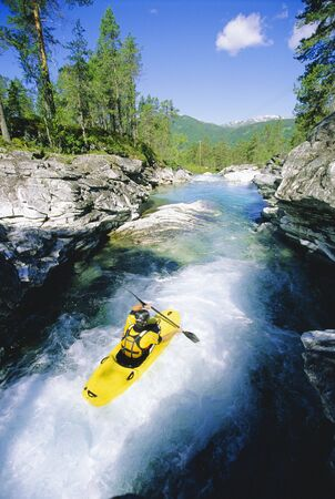 Kayaker rowing in rapids photo