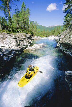 rapid: Kayaker rowing in rapids
