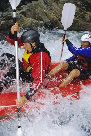 Two kayakers rowing in rapids and smiling (selective focus)
