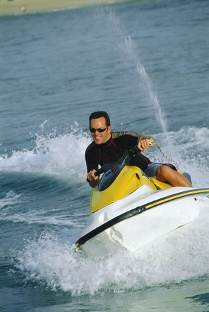 caucasoid race: Man jet skiing and smiling (selective focus)