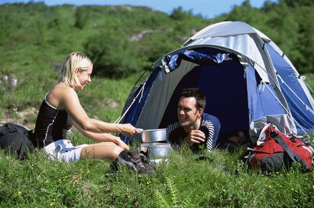 campsite: Couple outdoors at campsite with pots smiling (selective focus)
