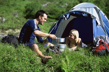 Couple outdoors at campsite with pots smiling (selective focus) photo