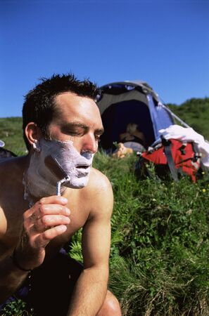 campsite: Man outdoors shaving at campsite with woman in background (selective focus)