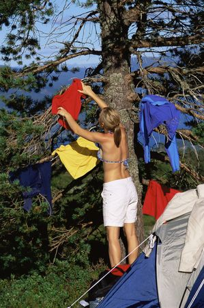 campsite: Woman outdoors at campsite hanging up wet clothes Stock Photo