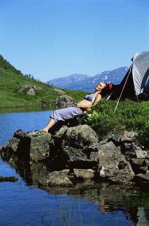 campsite: Woman outdoors at campsite sleeping on large rocks by lake Stock Photo