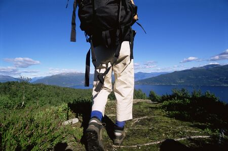 knap sack: Womans legs outdoors while hiking in scenic location Stock Photo