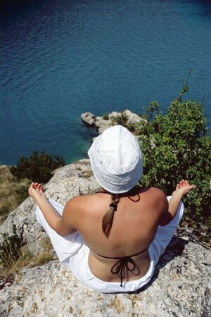 Woman outdoors doing yoga on cliff photo